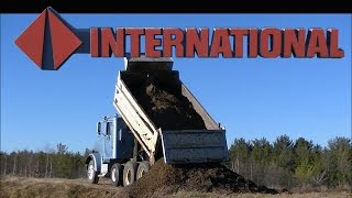 CAT 416 Loading the International Dump Truck with Gravel and Dumping It