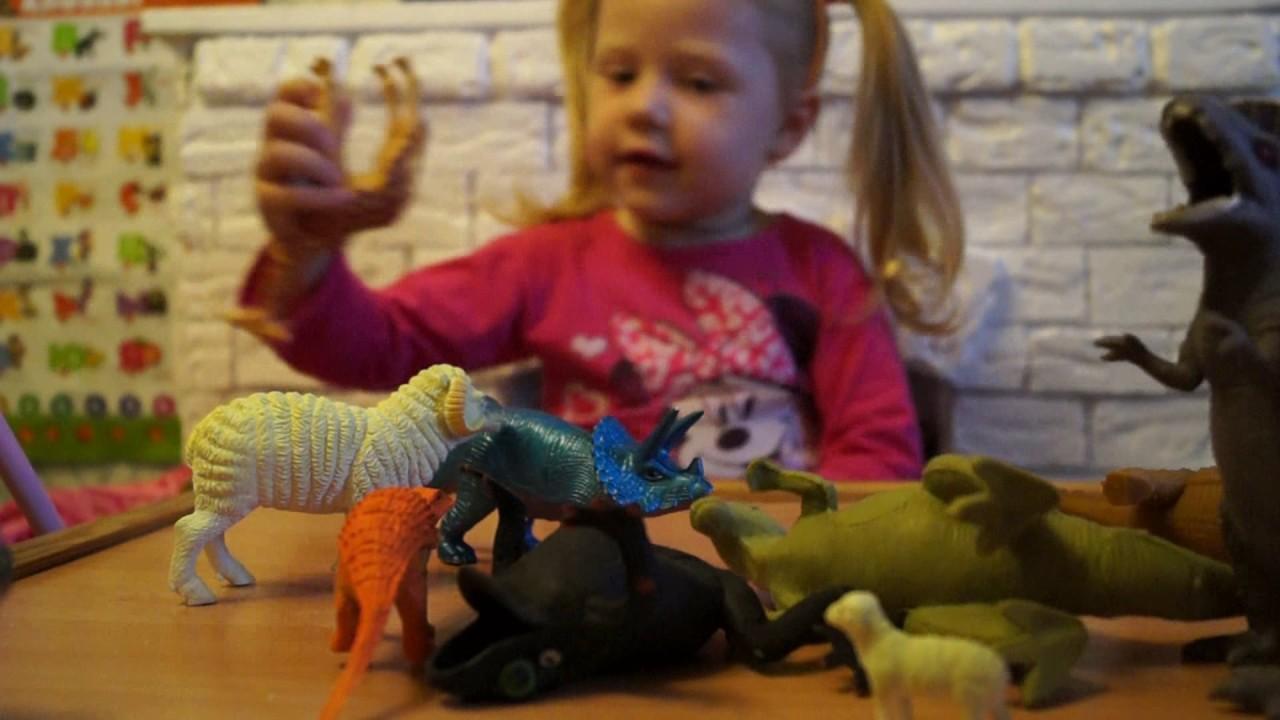 Показывает свои мягкие игрушки, игрушки из пластмассы ...