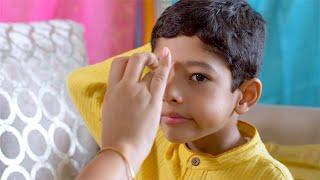 Raksha Bandhan - Little boy patiently sits while his sister applies tilak on his forehead