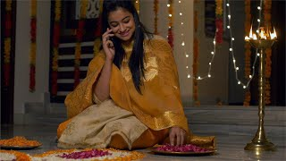Diwali celebration and decoration - Pretty Indian girl in traditional dress speaking over the phone and making flower rangoli