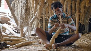 A worker preparing parts for making Ma Durga Idol with hay