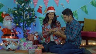 Young cute couple exchanging festival gifts while sitting under a decorated Christmas tree