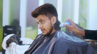 Hairdresser is cleaning young man's neck with the brush after haircut