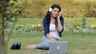 Girl sitting outdoor with laptop enjoying music on headphones