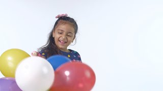 Beautiful Indian girl having fun with colored air balloons - kids leisure time