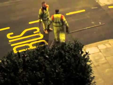 Workers paint letters on the street