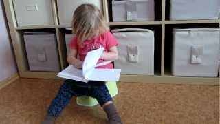Small baby girl reads on the potty