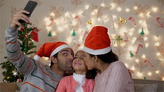 Happy Indian family in santa hats taking selfie near Christmas tree