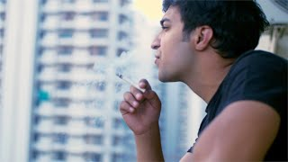 Young Indian man smoking a cigarette in the balcony