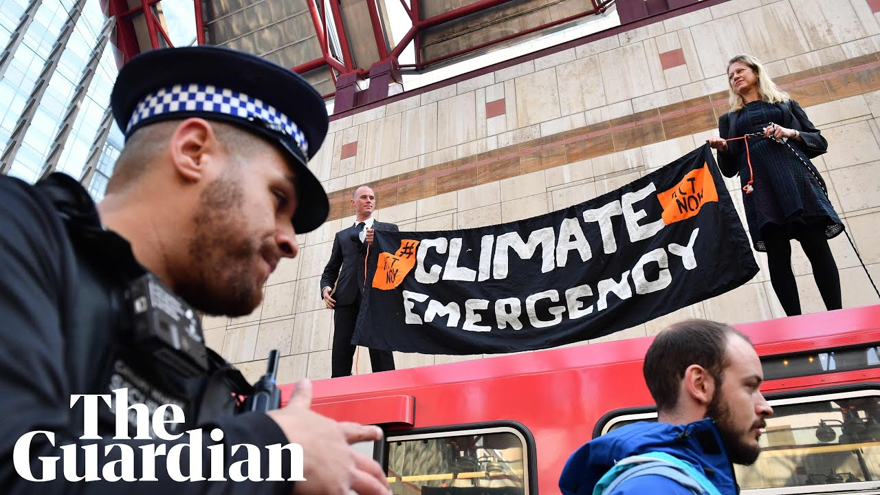 Image result for guardian: Climate protesters climb on top of train at Canary Wharf