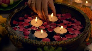 Diwali decoration - woman decorating her house with floating candles in a bowl / urli