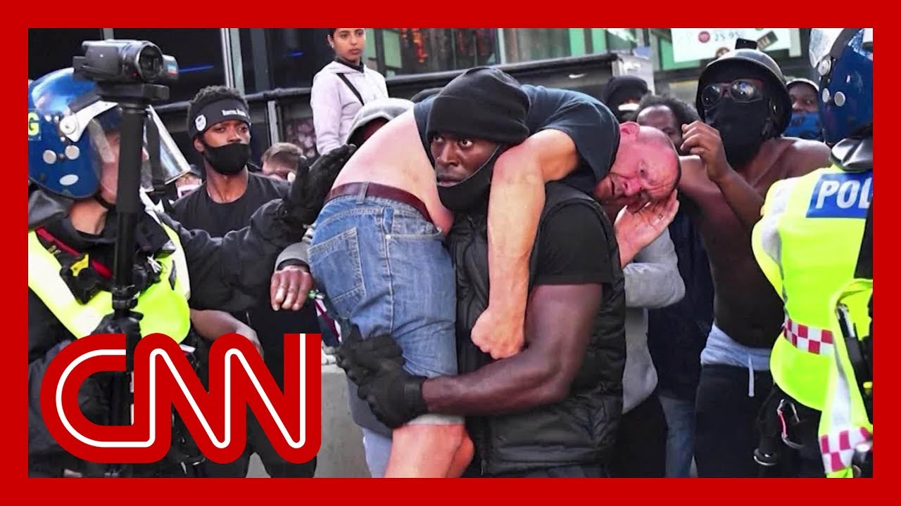 Black Lives Matter demonstrator carries injured white protester to safety in powerful image