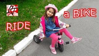 Lady Tamilla катается на трехколесном велосипеде. Lady Tamilla rides a bike