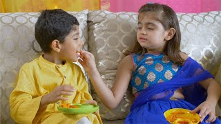 Shot of pretty Indian girl feeding french fries to her younger brother