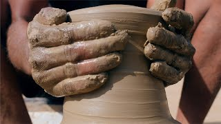 A closeup shot of a potter shaping the mud clay to make an earthen pot