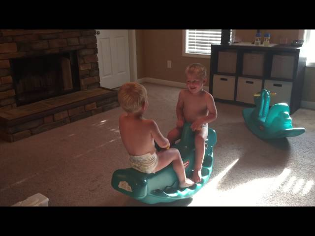 Twin brother having giggles on teeter totter