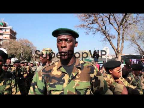 Long tracking shot of veteran soldiers singing and marchi...