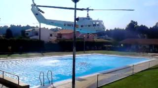 Helicopter refills its water bucket from a public swimming pool