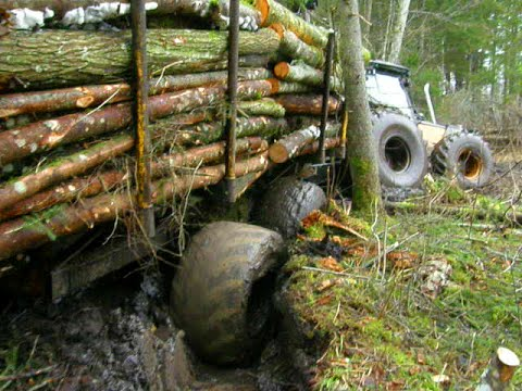 Valtra forestry tractor stuck in mud with big, fully loaded trailer