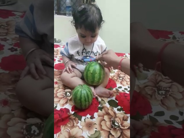Little girl baby playing with watermelon