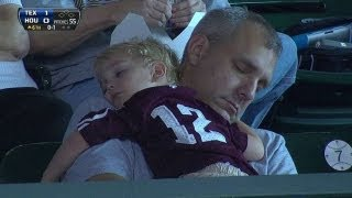 A young fan and his dad take a nap in crowd