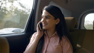 Young office woman talking to someone on her smartphone in her car after work