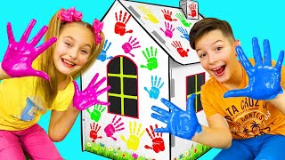 Sasha paints Cardboard Playhouses with colored Hands