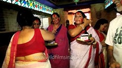 Women applying vermillion bindi to each other: Kolkata Durga puja