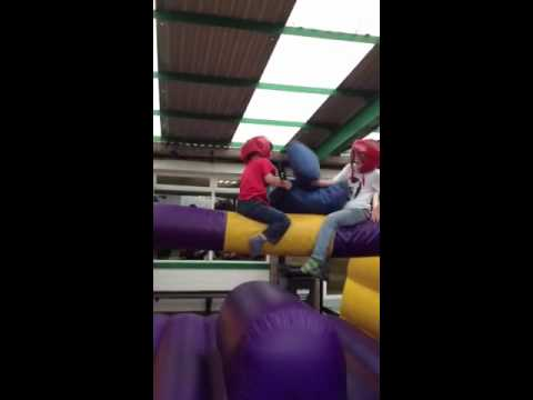 Boys pillow fighting on inflatable