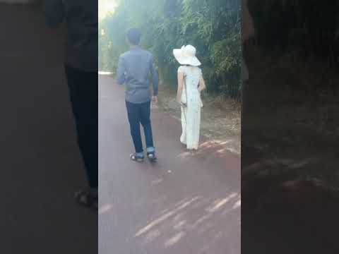 Chinese LHD amputee one leg lady strolling in the park on one crutch gracefully with her boyfriend