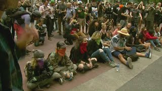 Far-left protesters sit in downtown Portland street