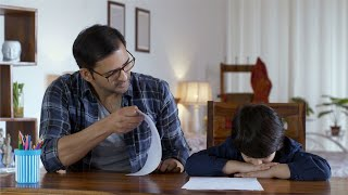 Indian father scolding his son looking at his exam paper. Small Family - Angry father and depressed little boy