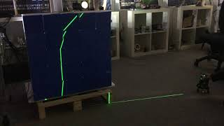 Green laser plane projected on a wall of square panels