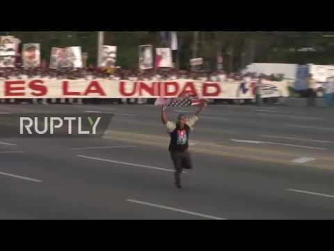 Cuba: Man with US FLAG sprints in front of May Day march in Havana