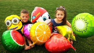 Kids hide and seek play with fruit balloons on the park