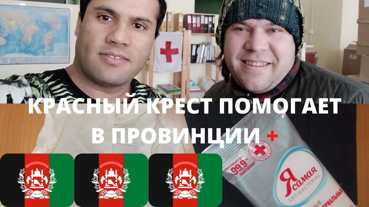 Красный крест и парень из Афганистана по имени Мирвайс помогает Волонтером