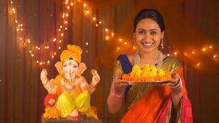 Beautiful Indian woman with flowers on pooja thali - celebrating Ganesh Chaturthi. Festival concept