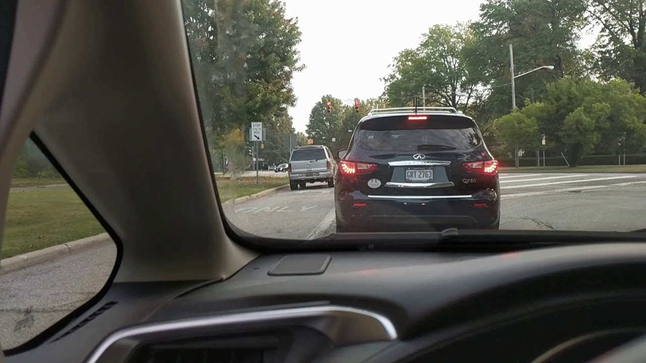 Cadillac SUV with license plate cover cutting off line of cars ...