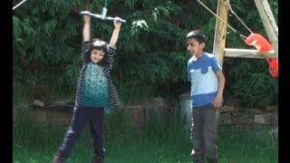 Kids Playing On A Spinning  Twizzler Hanging From Swing Frame