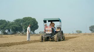 Middle-aged peasant tilling the land for cultivation by using a tractor in India