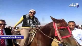 بالفيديو والصور .. الشاعرة البدوية تتحدى الرجال فى ماراثون الخيول العربية بالفيوم