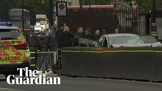 Westminster car crash: handcuffed man taken away by police