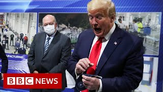 Trump removes mask before facing cameras at factory - BBC News