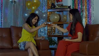 Two Indian female friends happily chatting during New Year or Christmas celebration