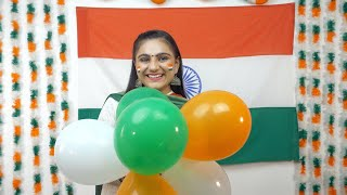 Indian girl smiles and poses for the camera - tri-color balloons in her hand. National flag. Independence Day