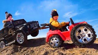 Лёва весело играя помогает вытащить застрявшую в песке машинку