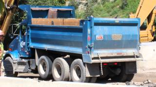 Blue Kenworth Dump Truck driving in and dumping his load of dirt into the trench