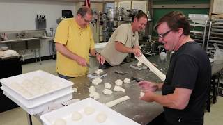 Chef Frank Murphy makes pizza dough with Mr Jake Smith and Mr Mike Forrester