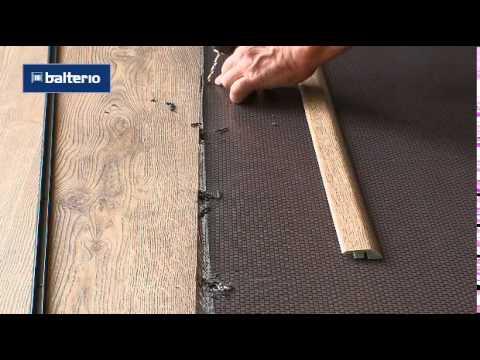 Установка переходного профиля между ламинатом и плиткой