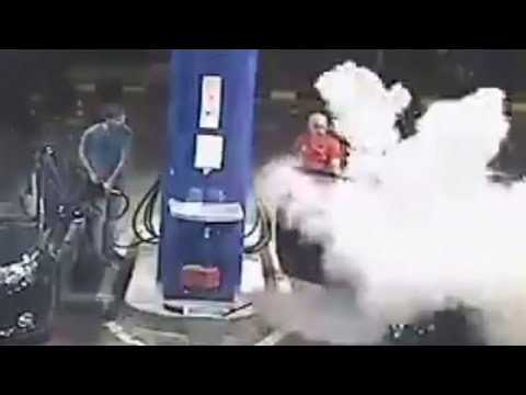 Gas station worker uses fire extinguisher on a man smoking cigarette at a gas station